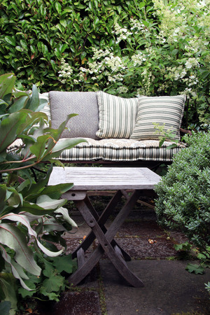 garden furniture: Cozy garden lounge chair with pillows, surrounded by green shrubs.
