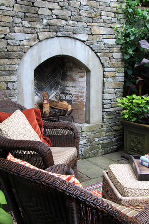 stone fireplace: Outdoor living. A fireplace, lounge chairs and coffee table in the garden. Stock Photo