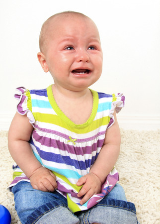 teething: Ten month old baby girl crying with teething pain.