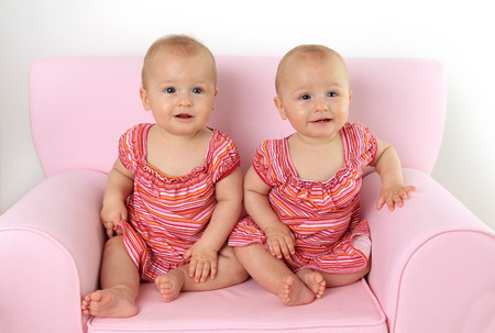 bare feet girl: Identical 10 month old twin baby girls seated on a pink child size sofa.