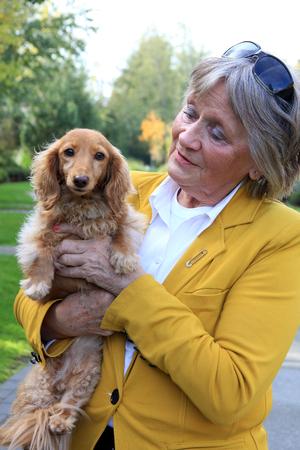 Senior woman holding a dachshund dog. Imagens