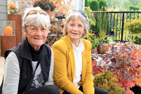Two senior ladies, age 76, seated outside on a wood deck during autumn.