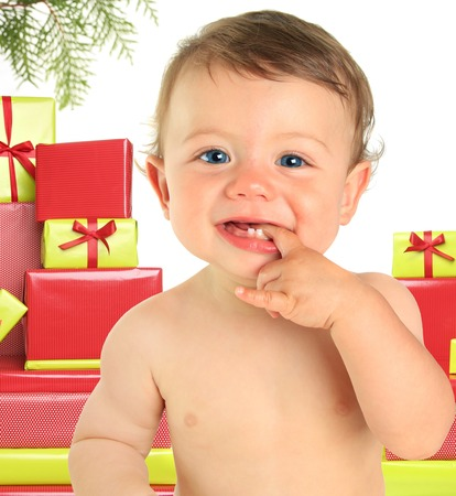 overindulgence: Adorable ten month old baby boy surrounded by Christmas gifts.
