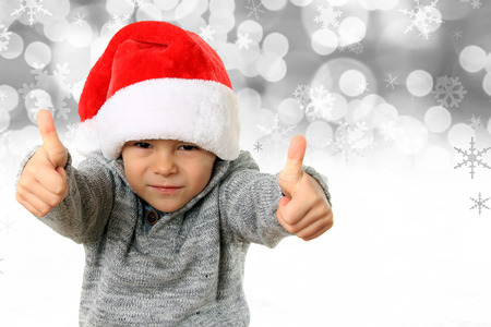 five year old: Five year old boy wearing a Santa hat with both thumbs up on a snowflake background.