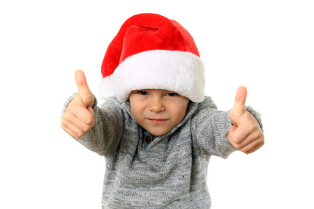 five year old: Five year old boy wearing a Santa hat with both thumbs up. Studio isolated.