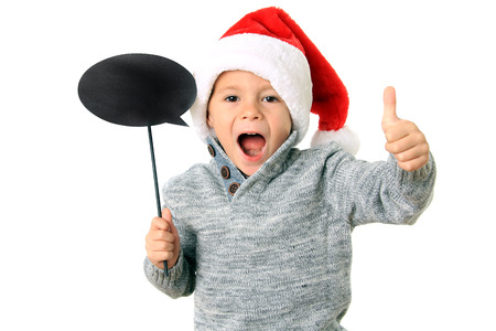 five year old: Five year old boy wearing a Santa hat with thumbs up and a speech bubble. Add your own text. Stock Photo