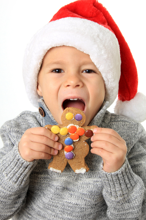 five year: Five year old boy wearing a Santa hat, eating a gingerbread man cookie.