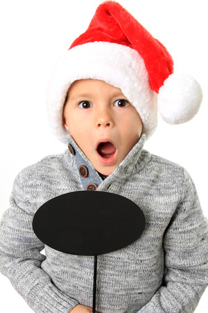 five year old: Five year old boy wearing a Santa hat holding a speech bubble. Add your own text.