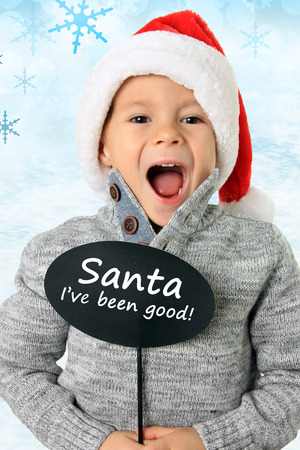 white hat: Five year old boy wearing a Santa hat holding a speech bubble.Also available without text.