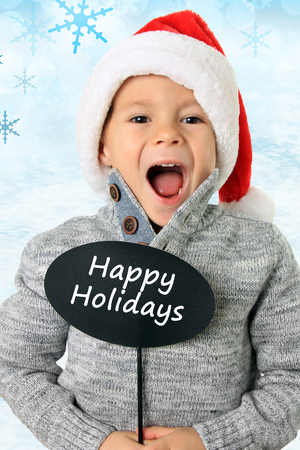 five year old: Five year old boy wearing a Santa hat holding a speech bubble that says Happy Holidays. Also available without text. Stock Photo
