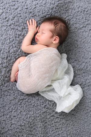 cute babies: Newborn baby girl asleep on a blanket.