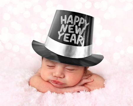 Newborn baby girl wearing a Happy New Year hat.