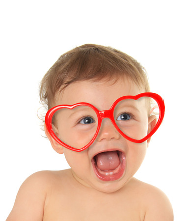 person smiling: Ten month old baby boy wearing heart shape valentine glasses.