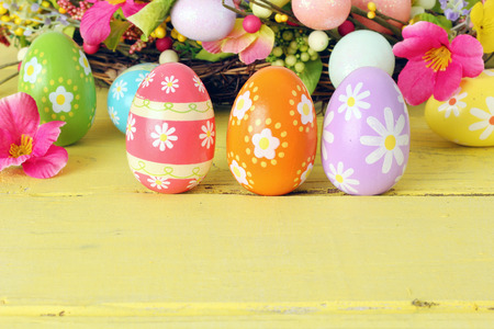 seaonal: Easter eggs and flowers on a sunny yellow background. Stock Photo