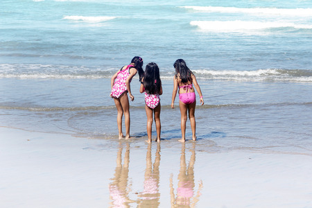 Three little girls standing on the beach. Stock Photo