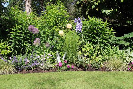 garden lawn: Perennial park garden flower bed in summer.