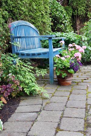 banco de jardín rústico y geranios de color rosa
