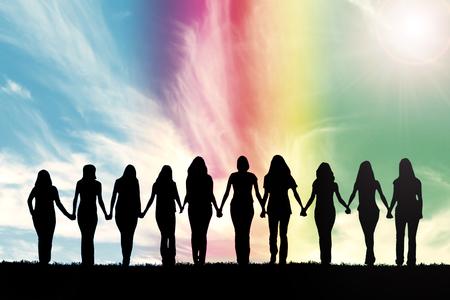Silhouette von zehn jungen Frauen, Hand in Hand unter einem Regenbogen Himmel.