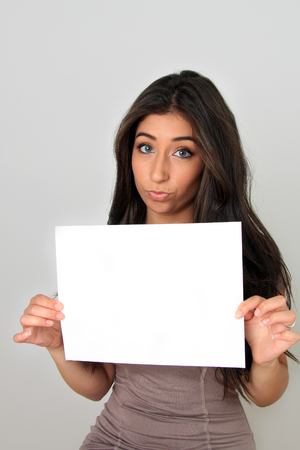 young add: Beautiful young woman holding a blank sign. Add your own text.