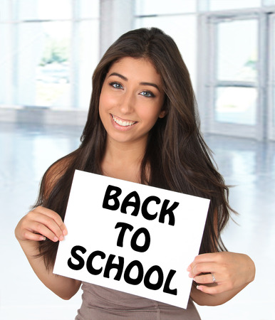 smiling face: Beautiful young woman holding a blank sign. Add your own text.