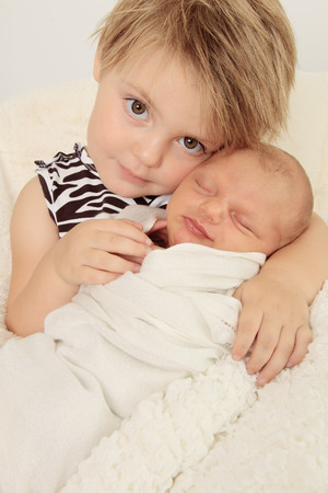 Newborn baby girl and her big sister.