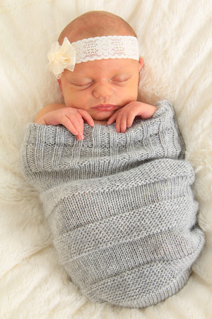 closed ribbon: Newborn baby girl asleep on a blanket.