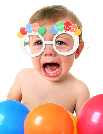 Angry crying baby boy wearing Happy Birthday glasses.