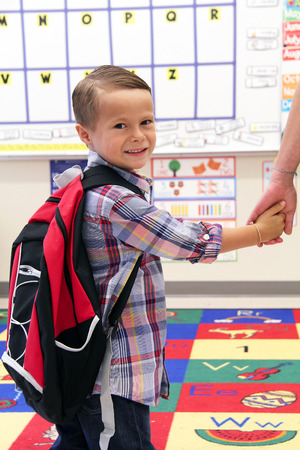 Young boy wearing a backpack, holding his mothers hand in the classroom. Stock Photo