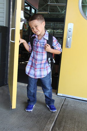 6 years: Young boy wearing a backpack entering the school. Back to school concept.
