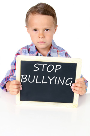 five year: Sad five year old boy with stop bullying message on a chalk board.