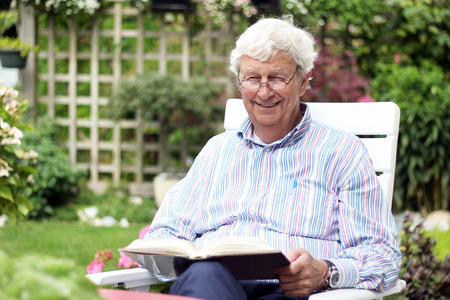 Happy retired gentleman age 78, reading a book in the garden. Visible hearing aid. Stock Photo