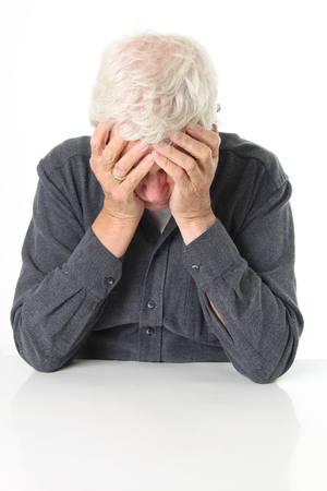 lonelyness: Senior man age 78 depressed with head in his hands.