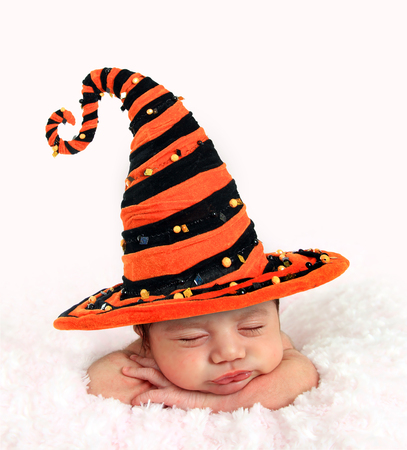 Newborn baby girl wearing a Halloween witch hat. Stock Photo