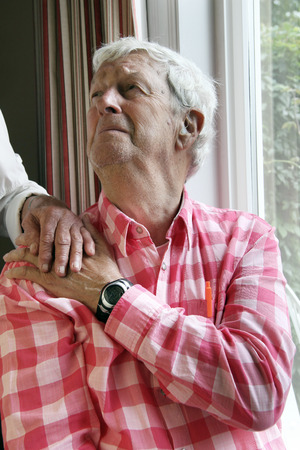 alzheimers: Senior gentleman age 7  looking upward with despair. Wifes hand on his shoulder.