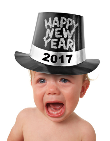 Crying baby boy wearing a Happy New Years hat, studio isolated on white. Stock Photo
