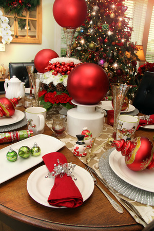 table set: Christmas table set for Christmas day breakfast with holiday floral arrangements, baubles and ornaments.