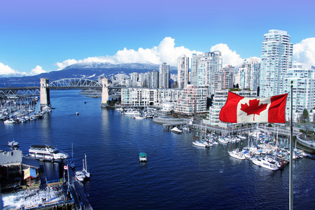 daytime: Canadian flag in front of view of False Creek and the Burrard street bridge in Vancouver, Canada.