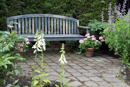 Rustic wooden garden bench and pink geraniums. Also available in vertical.