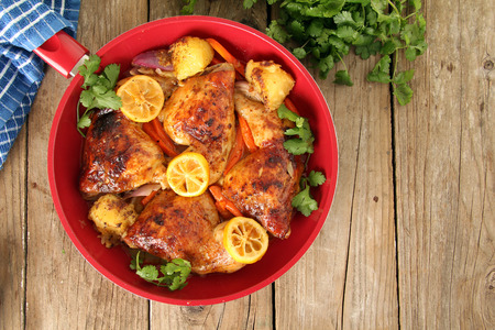Roasted free range organic Chicken dinner with potatoes, carrots, lemon and cilantro.  Stock Photo