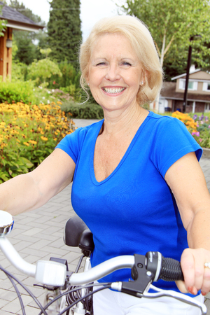 Happy smiling beautiful seventy year old lady on a bicycle.  photo