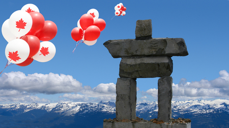 Canada Balloons with maple leaf floating over an inukshuk in the Rocky mountains. Stock Photo