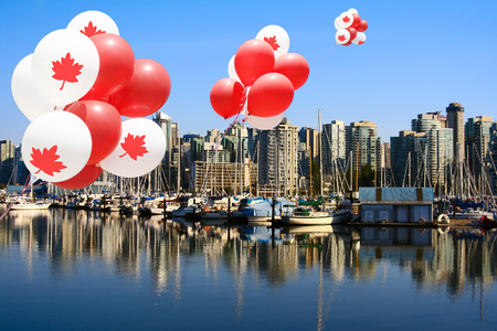 highrises: Canada day maple leaf balloons floating over Vancouvers Coal Harbor.