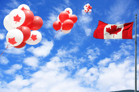 Canadian maple leaf flag and balloons in the sky for Canada day.