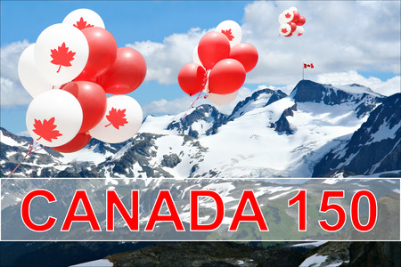 Canada day Maple leaf balloons floating over the Rocky mountains with a Canadian flag in the distance for Canadas 150 Birthday celebration. Stock Photo