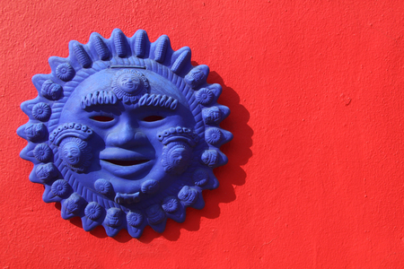 Mayan sun handicraft on a bright red wall in Mexico.