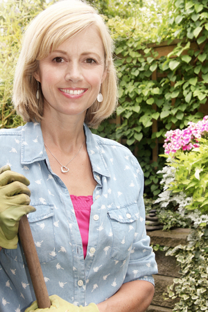 Smiling blond woman gardener holding a rake in a small garden. photo