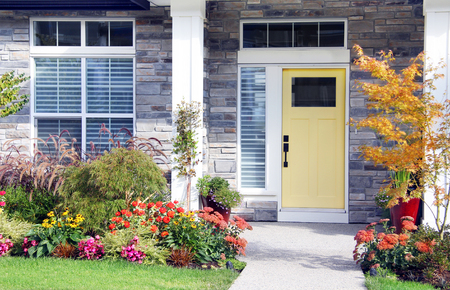 Pretty new home with a colourful front door and perennial garden. Stock Photo