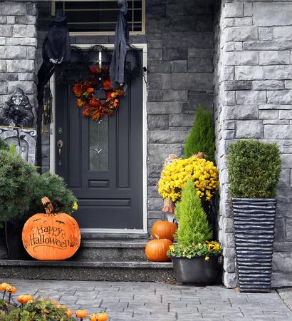 Voordeur naar een huis versierd met Halloween pompoenen