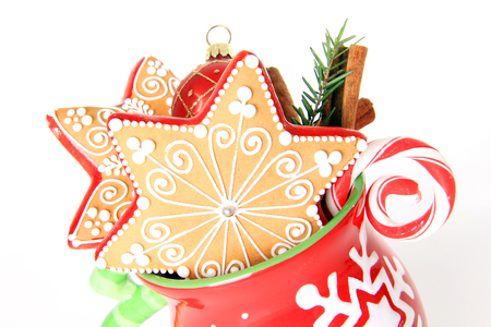 professionally: Professionally decorated Christmas cookies in a holiday mug with a candy cane and holiday bauble. Stock Photo