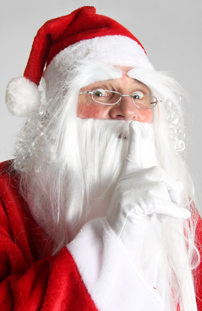 Christmas Santa Claus holding a finger to keep quiet.  Stock Photo